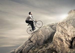 Businessman-riding-bike-up-rocky hill