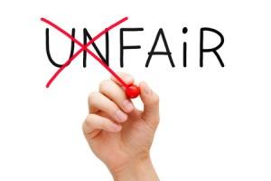 A hand making word Unfair into Fair
